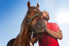 Homem novo com seu cavalo de baía contra o céu azul Imagem de Stock Royalty Free