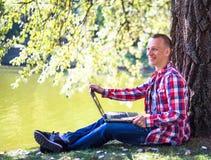 Homem novo com seu portátil no parque da cidade exterior Fotografia de Stock