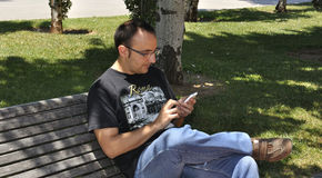 Homem novo com seu smartphone Imagem de Stock