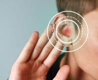 Homem novo com sintoma da perda da audição no fundo da cor fotos de stock royalty free