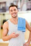 Homem novo com smartphone e toalha no gym Fotos de Stock Royalty Free