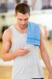 Homem novo com smartphone e toalha no gym Fotografia de Stock