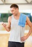 Homem novo com smartphone e toalha no gym Fotos de Stock