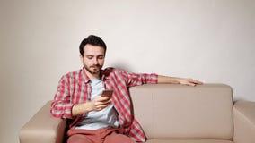 Homem novo com smartphone em casa filme