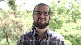Homem novo com sorriso feliz do retrato da barba Parte externa feliz de sorriso do homem farpado novo considerável que olha a câm vídeos de arquivo