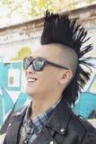 Homem novo com sorriso punk do Mohawk e dos óculos de sol fotos de stock