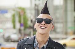 Homem novo com sorriso punk do Mohawk e dos óculos de sol imagens de stock royalty free