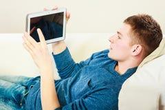 Homem novo com a tabuleta digital que coloca no sofá imagem de stock royalty free