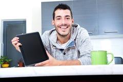 Homem novo com a tabuleta na cozinha fotos de stock royalty free