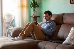Homem novo com a tabuleta no sof? em casa fotos de stock