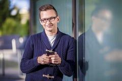 Homem novo com telefone móvel Fotografia de Stock Royalty Free