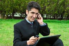 Homem novo com telefones e portátil de pilha. Imagens de Stock