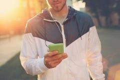 Homem novo com texto de datilografia do telefone celular e passeio na rua fotografia de stock