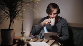Homem novo com toque do PC da tabuleta em um café que tem algum copo de café Foto de Stock