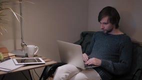 Homem novo com toque do PC da tabuleta em um café que tem algum copo de café Fotografia de Stock