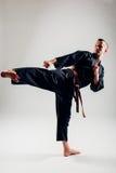 Homem novo com treinamento alaranjado do lutador do karaté da correia Fotografia de Stock