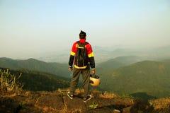 Homem novo com trouxa e capacete que está com mãos levantadas sobre uma montanha e que aprecia a opinião do vale Imagem de Stock