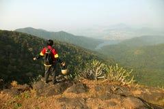 Homem novo com trouxa e capacete que está com mãos levantadas sobre uma montanha e que aprecia a opinião do vale Foto de Stock