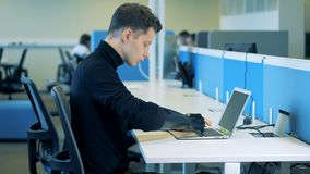 Homem novo com um braço artificial que senta-se e que datilografa em um teclado Conceito robótico do braço do cyborg vídeos de arquivo