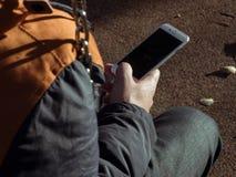 Homem novo com um dispositivo móvel Fotografia de Stock Royalty Free