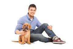 Homem novo com um filhote de cachorro do corso do bastão Foto de Stock