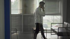 Homem novo com um olhar da barba no wondow e no pensamento Homem de negócio no escritório que pensa sobre investimentos cortinas  vídeos de arquivo