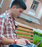 Homem novo com um portátil no banco. imagem de stock