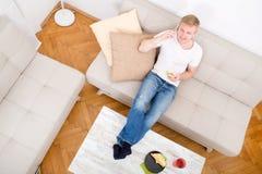 Homem novo com um sanduíche no sofá Foto de Stock Royalty Free
