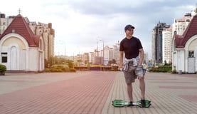 Homem novo com um skate em uma rua da cidade Fotos de Stock