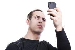 Homem novo com um smartphone fotos de stock