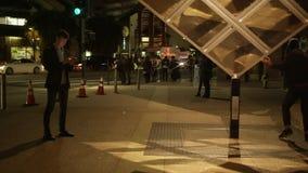 Homem novo com um smartphone em um cubo de giro próximo da rua video estoque