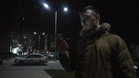 Homem novo com um telefone na rua video estoque