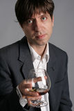 Homem novo com um vidro do conhaque Imagens de Stock Royalty Free