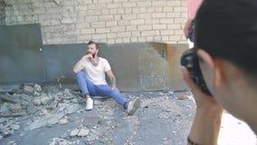 Homem novo com uma barba bonita em uma camiseta de alças branca contra uma parede de tijolo cinzenta vídeos de arquivo