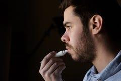 Homem novo com uma barba que repara seus bordos danificados com creme hidratante fotos de stock royalty free