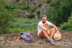 Homem novo com uma barba que senta-se no penhasco da garganta Imagens de Stock Royalty Free