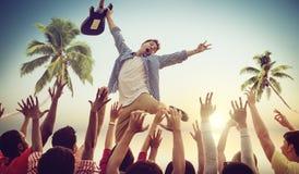 Homem novo com uma guitarra que executa em uma praia concentrada Fotografia de Stock Royalty Free