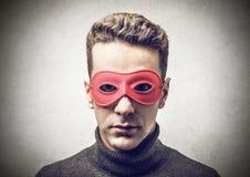 Homem novo com uma máscara vermelha imagens de stock