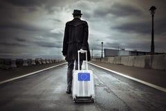 Homem novo com uma mala de viagem do rolamento com uma bandeira europeia Foto de Stock