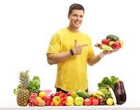 Homem novo com uma placa que aponta atrás de uma tabela com fruto e VE Fotografia de Stock Royalty Free
