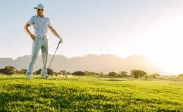 Homem novo com a vara do golfe no campo Imagens de Stock