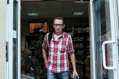 Homem novo comprado uma garrafa da vodca Foto de Stock Royalty Free