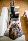 Homem novo concentrado com funcionamento de vidros em um portátil em um escritório domiciliário Cópias no teclado, varreduras o t fotos de stock royalty free