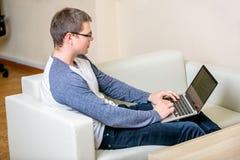 Homem novo concentrado com funcionamento de vidros em um portátil em um escritório domiciliário Datilografe em um teclado e em um fotos de stock