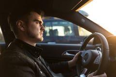 Homem novo concentrado que conduz um carro luxuoso imagem de stock