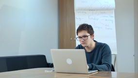 Homem novo concentrado que usa o portátil na sala de classe Imagem de Stock Royalty Free