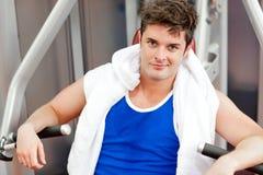 Homem novo confiável com uma toalha usando a imprensa de banco Fotos de Stock