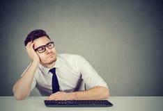 Homem novo confundido na mesa de trabalho imagens de stock royalty free