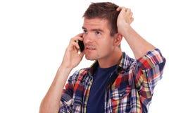Homem novo confuso no telefone Fotografia de Stock Royalty Free