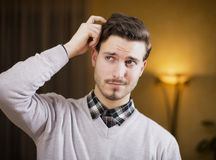 Homem novo confuso ou duvidoso que risca sua cabeça e que olha acima Imagens de Stock